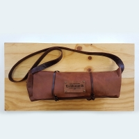 A closed, handcrafted leather saddlebag