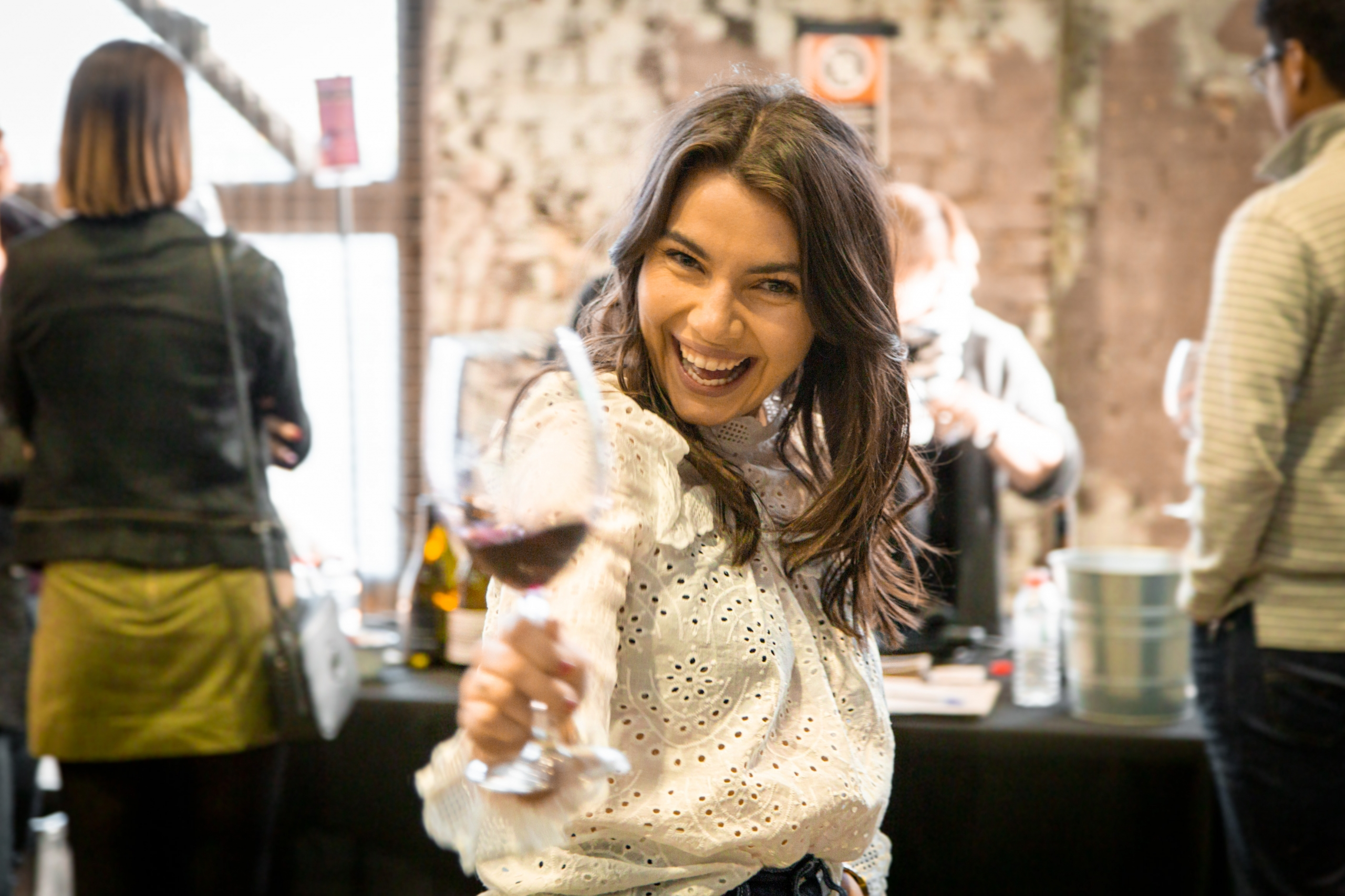 A woman in a white top smiling and holding out a glass of red wine at a Barossa wine event