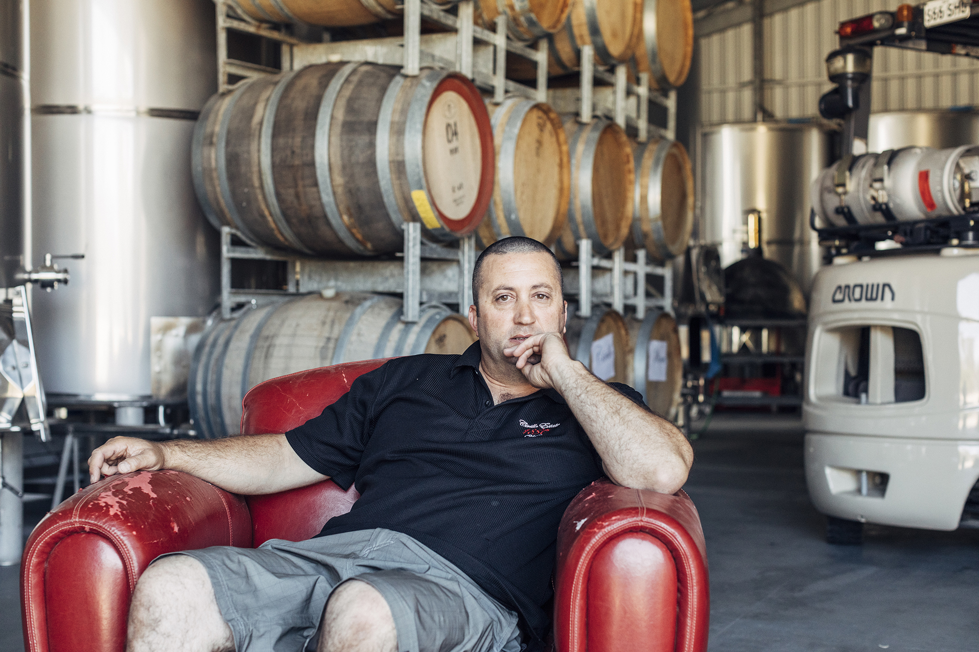 Marco Cirillo of Cirillo Estates Wines sitting in a red chair in his winery