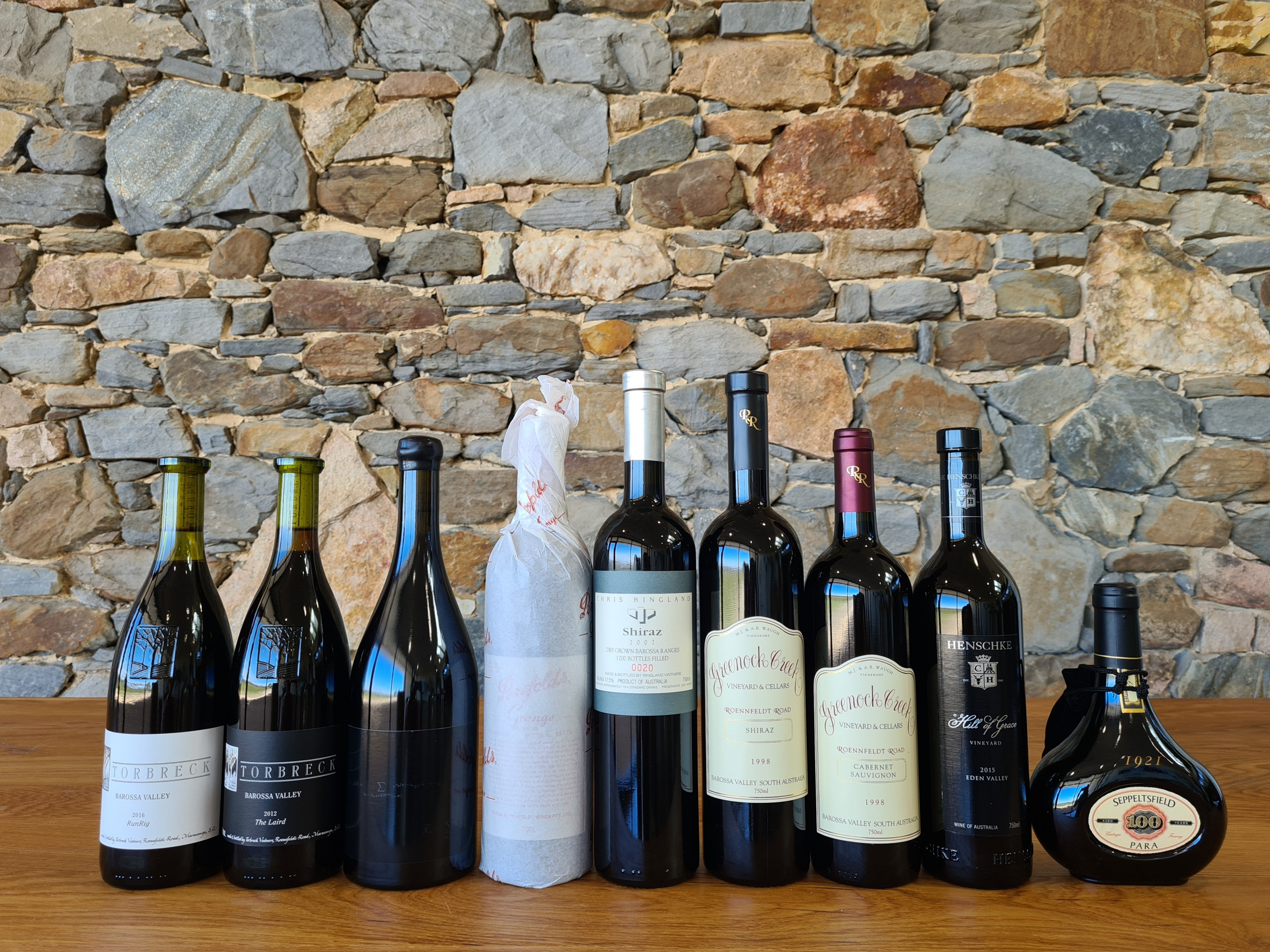 9 bottles of 100 point Barossa wine sitting on a wooden table in front of a stone wall